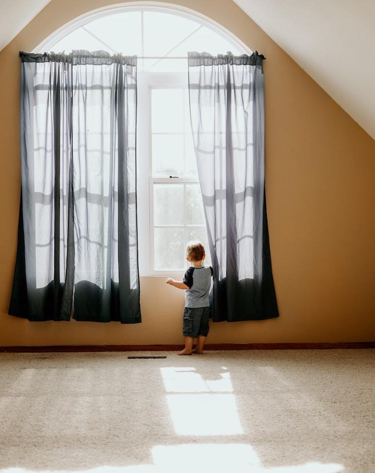 Toddler standing on clean, healthy carpet and looking out window