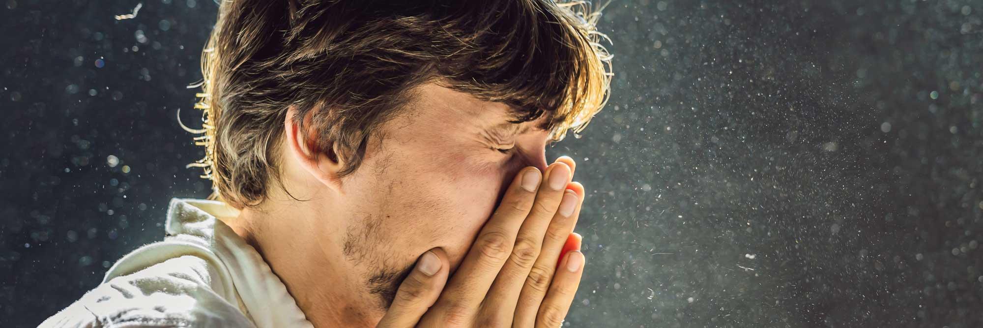 Man with allergies sneezing